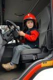 De jongen zit in een brandvrachtwagen Stock Foto