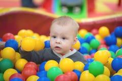 De jongen zit in een stapel van ballen in een droge pool en speelt royalty-vrije stock foto's