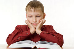 De jongen zit en leest een boek royalty-vrije stock fotografie
