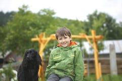 De jongen zit met de hond royalty-vrije stock fotografie