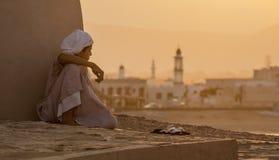 De jongen zit naast een muur lettend op de zonsondergang Stock Foto