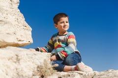 De jongen zit op de bovenkant Royalty-vrije Stock Foto