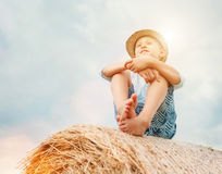 De jongen zit op de hooibergbovenkant met zonnige hemelachtergrond Stock Afbeelding