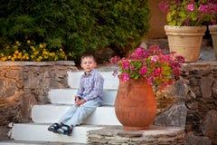 De jongen zit op de stappen in tuin Stock Foto's