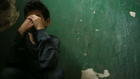 De jongen zit op de stappen van een verlaten portiek Het concept kinderen` s drugsverslaving, landloperij, dakloosheid stock video