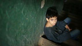 De jongen zit op de stappen van een verlaten portiek Het concept kinderen` s drugsverslaving, landloperij, dakloosheid stock footage