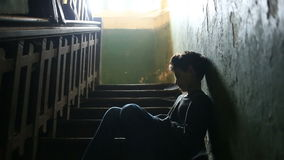 De jongen zit op de stappen van een verlaten portiek Het concept kinderen` s drugsverslaving, landloperij, dakloosheid stock videobeelden