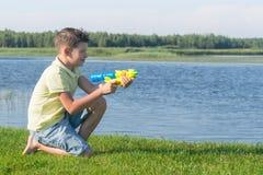 De jongen zit op het gras en schiet water van een pistool op het meer in de zomer stock foto's