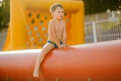 De jongen zit op trampoline droevige drie-jaar-oude kindzitting op een opblaasbare voetbalpool Stock Foto's