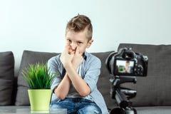 De jongen zit voor een SLR-camera, close-up Blogger, het blogging, technologie, inkomens op Internet De ruimte van het exemplaar royalty-vrije stock foto