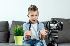 De jongen zit voor een SLR-camera, close-up Blogger, het blogging, technologie, inkomens op Internet De ruimte van het exemplaar royalty-vrije stock foto's