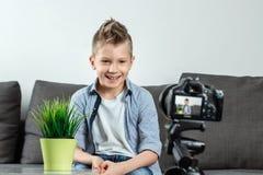 De jongen zit voor een SLR-camera, close-up Blogger, het blogging, technologie, inkomens op Internet De ruimte van het exemplaar stock foto