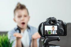De jongen zit voor een SLR-camera, close-up Blogger, het blogging, technologie, inkomens op Internet De ruimte van het exemplaar royalty-vrije stock afbeelding