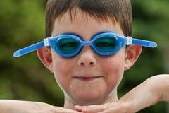 De jongen zwemt binnen Beschermende brillen Stock Afbeelding