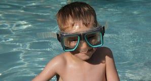 De jongen zwemt binnen Beschermende brillen Stock Fotografie