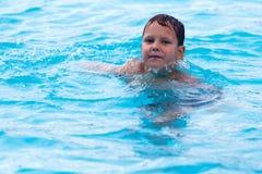 De Jongen zwemt in de pool stock afbeelding