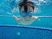 De jongen zwemt onderwater in de pool Stock Foto's