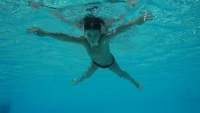 De jongen zwemt in zwembad, onderwater langzame motie