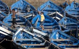 De jongens bevinden zich onder de vele vissersboten in de haven van Essouaira, Marokko Royalty-vrije Stock Afbeelding