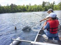 De jongens die in een kano vissen vangen een snoekbaars Stock Afbeeldingen