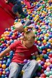 De jongens die in kleurrijke bal spelen voegen samen Stock Fotografie