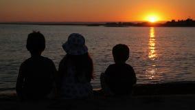 De jongens en het meisje letten op de zonsondergang stock footage