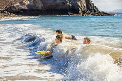 De jongens hebben pret in de oceaan met hun boogieraad Royalty-vrije Stock Fotografie