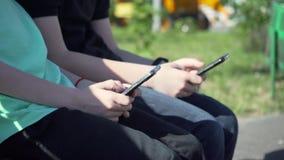De jongens met zwarte smartphone zit op de bank De kleine jongens met celtelefoon zit op de bank in tuin De jonge geitjes communi stock footage