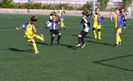 De jongens op het Voetbal van de Jeugd van de Stad van Alicante vormen tot een kom Stock Foto