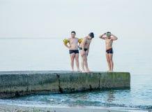 De jongens treffen om van de pijler in het overzees te springen voorbereidingen stock foto