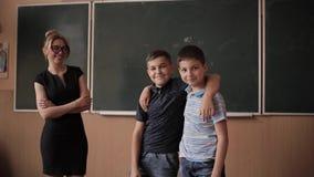 De jongens van de leraarshulp door het bord Jonge vrouwelijke leraarsstudie stock footage