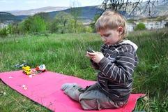 De jongens verkiezen mobiles aan speelgoed stock foto's