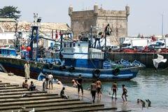 De jongens zwemmen in de visserijhaven in Essaouira in Marokko Stock Foto's