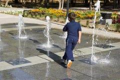 De jongenslooppas rond in de fontein Stock Foto's