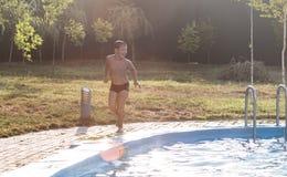 De jongenslooppas rond de pool stock foto