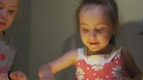 De jongensmeisjes trekken beelden met vingers op zand in kleuterschool stock video