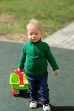 De jongenspeuter die van de één éénjarigebaby groene sweater dragen bij speelplaats Stock Afbeeldingen