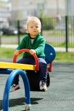 De jongenspeuter die van de één éénjarigebaby groene sweater dragen bij speelplaats Stock Foto's