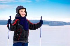 De jongensskiër van het jonge geitje over blauwe hemel Royalty-vrije Stock Fotografie