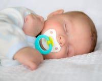 De jongensslaap van de zuigelingsbaby met fopspeen Stock Afbeeldingen