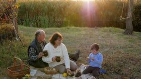 De jongensspelen met egel in openlucht naast grootouder met kop theeën zitten op achtergrondzonsondergang stock video