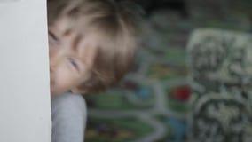 De jongensspelen met gelaatsuitdrukkingen Een kleine jongen kijkt uit van rond de hoek, maakt gezichten, heeft pret stock video