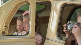 De jongensspelen met retro de camera die uit een venster van de beige retro auto leunen Het grote bedrijf van kleine kinderen stock videobeelden