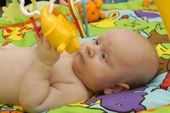 De jongensspelen van de baby met stuk speelgoed Stock Fotografie