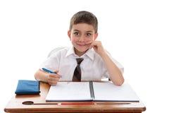 De jongensstudent van de school bij bureau stock foto