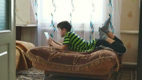 De jongenstiener ligt spelend op tabletspel doorbladerend Internet stock video