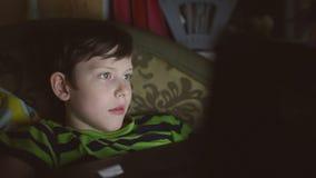 De jongenstiener met laptop computer speelt het spel op Internet stock video