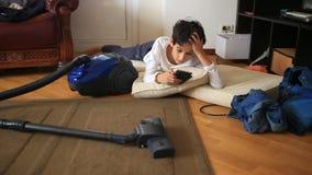 De jongenstiener onttrekt aan zich haar thuiswerk, die op haar mobiele telefoon spelen Het schoonmaken van de kinderen` s ruimte  stock video