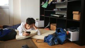 De jongenstiener onttrekt aan zich haar thuiswerk, die op haar mobiele telefoon spelen Het schoonmaken van de kinderen` s ruimte  stock footage