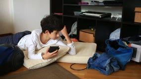 De jongenstiener onttrekt aan zich haar thuiswerk, die op haar mobiele telefoon spelen Het schoonmaken van de kinderen` s ruimte  stock videobeelden